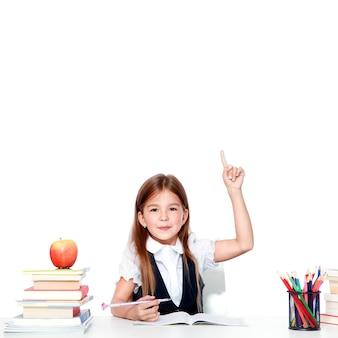 Feliz y linda colegiala adolescente levantando la mano en el aula