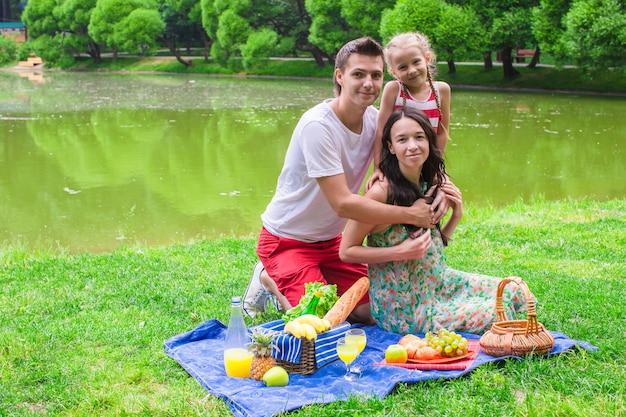 Feliz linda familia de tres picnic al aire libre