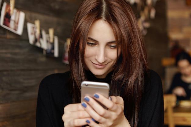 Feliz linda joven con amigos de mensajería de cabello largo y oscuro en línea usando un dispositivo de teléfono inteligente moderno o navegando en las redes sociales. chica guapa disfrutando de conexión inalámbrica a internet en la cafetería.