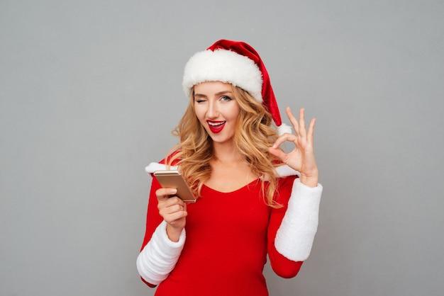 Feliz linda joven en traje de santa con teléfono celular y mostrando signo ok sobre superficie gris