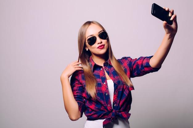 Feliz linda mujer haciendo selfie aislado sobre pared gris.