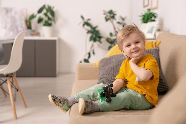 Feliz lindo niño rubio en ropa casual sentado en un sofá suave en la sala de estar y jugando con un coche de juguete en el entorno doméstico