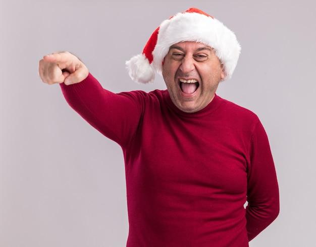 Feliz loco hombre de mediana edad vestido con gorro de papá noel de navidad apuntando con el dedo índice a algo parado sobre la pared blanca