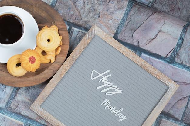 Feliz lunes en el tablero con una taza de bebida y galletas alrededor