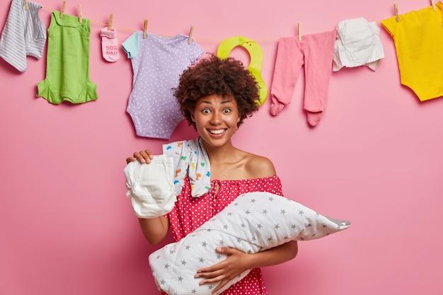 Feliz madre afroamericana se preocupa por el bebé, cambia el pañal a la hija, juega con el niño, se para en el interior de la casa, posa