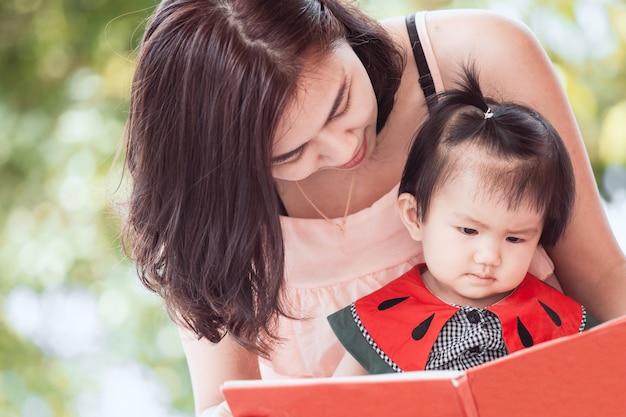 Feliz madre asiática y linda niña bebé leyendo un libro junto con la diversión y el amor