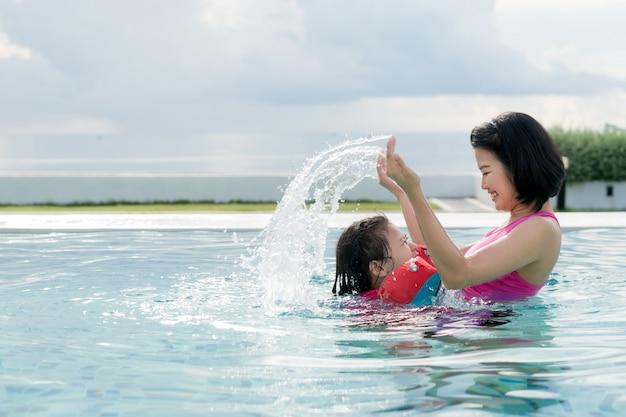 Feliz madre asiática y su hija divirtiéndose en la piscina del hotel