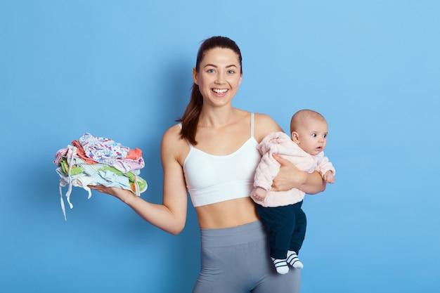 Feliz madre atractiva con bebé aislado sobre fondo azul, dama con hija recién nacida mira a la cámara con una sonrisa encantadora, sostiene pila de ropa para niños, cuida al niño durante la licencia de maternidad