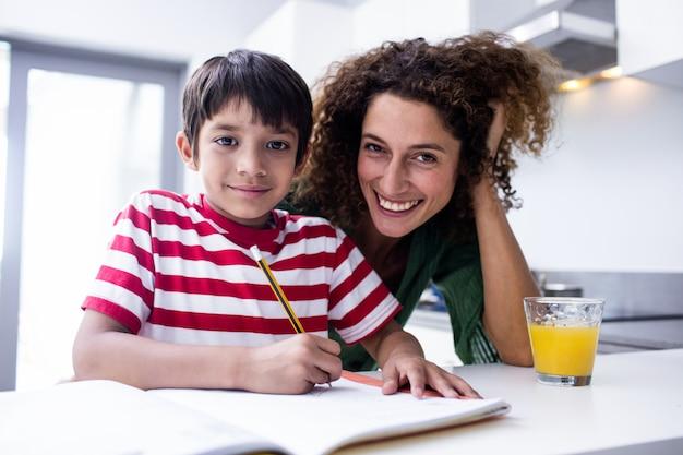 Feliz madre ayudando a hijo con la tarea