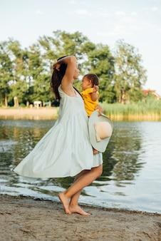 Feliz madre y bebé abrazando en la playa del río