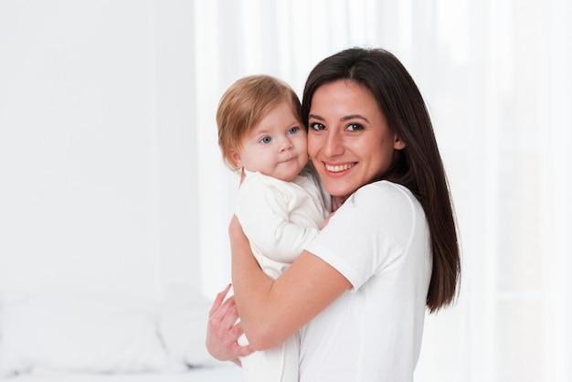 Feliz madre y bebé posando