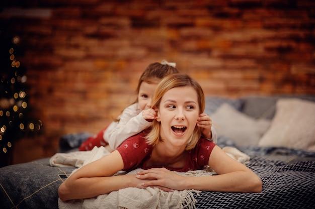 Feliz madre de cabello rubio en pijama rojo con hija bromeando sobre su espalda acostada en la cama gris mirando hacia los lados frente a la pared de ladrillo marrón y el árbol de navidad con luces de guirnalda