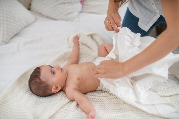 Feliz madre cariñosa viste cuidadosamente a su bebé recién nacido