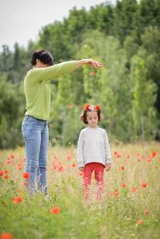 Feliz madre con su pequeña hija en el campo de amapola