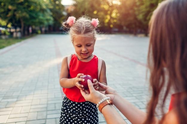 Feliz madre conoció a su hija después de clases al aire libre en la escuela primaria.
