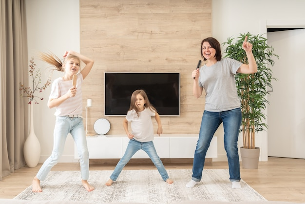 Feliz madre y dos hijas que se divierten cantando canciones de karaoke en cepillos para el cabello. madre riendo disfrutando de una divertida actividad de estilo de vida con una adolescente en casa juntos.