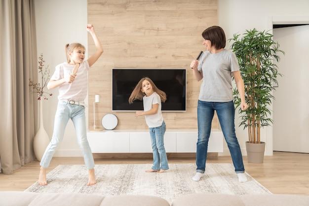 Feliz madre y dos hijas que se divierten cantando canciones de karaoke en cepillos para el cabello.