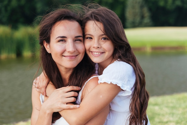 Feliz madre e hija abrazando al aire libre retrato