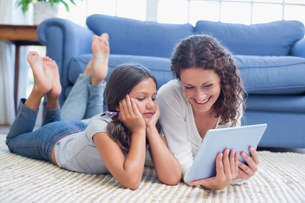 Feliz madre e hija acostada en el piso y uso de tableta