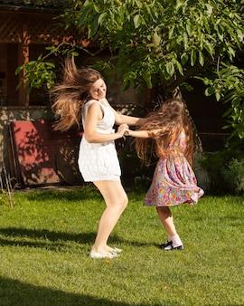 Feliz madre e hija bailando sobre el césped en un día soleado