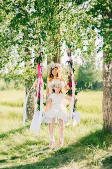 Feliz madre e hija balanceándose en los columpios verano soleado