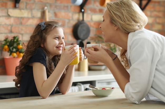 Feliz madre e hija desayunando en la cocina