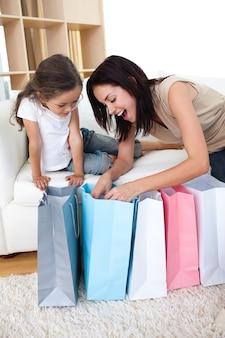 Feliz madre e hija desempacar bolsas de compras