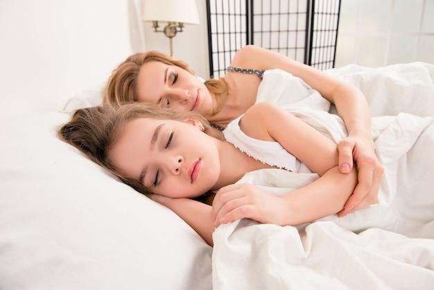 Feliz madre e hija durmiendo en la cama abrazando