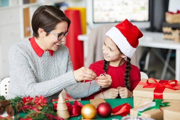 Feliz madre e hija envolver regalos de navidad