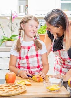 Feliz madre e hija están preparando un pastel juntos