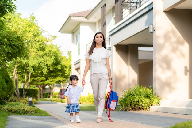 Feliz madre e hija estudiante de jardín de infantes caminando a la escuela en la rutina escolar matutina.