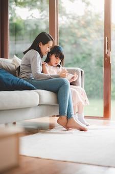 Feliz madre e hija de familia asiática con tableta digital para estudiar juntos en casa.