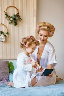 Feliz madre e hija hacen un maquillaje sentándose en la cama en el dormitorio