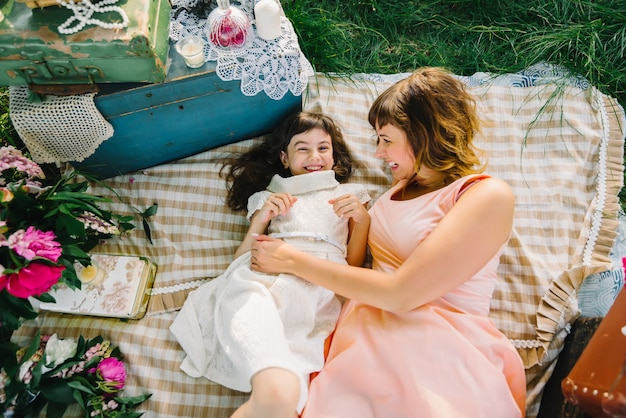 Feliz madre e hija jugando y sonriendo mientras está acostado sobre una manta en el verano