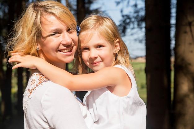 Feliz madre e hija en un paseo por el bosque. retrato