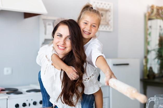 Feliz madre e hija posando con rodillo de cocina