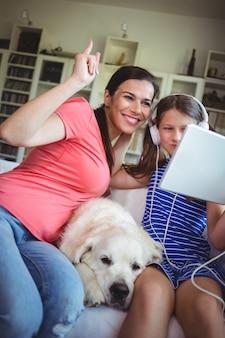 Feliz madre e hija sentada con un perro mascota y usando digital