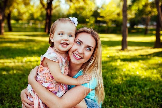 Feliz madre e hija sonriendo a la naturaleza