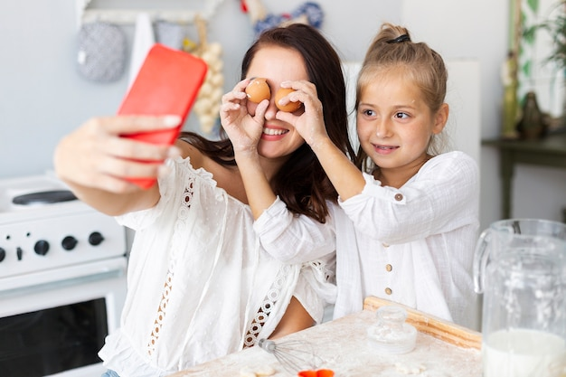 Feliz madre e hija tomando selfies con huevos