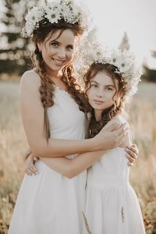Feliz madre e hija en vestidos blancos con coronas florales y trenzas de estilo boho en verano en un campo