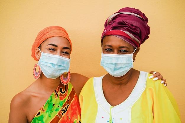 Feliz madre e hija con vestidos tradicionales africanos con mascarilla protectora