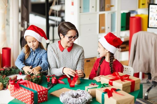 Feliz madre e hijas envolver regalos de navidad