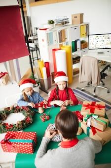 Feliz madre e hijas con regalos de navidad