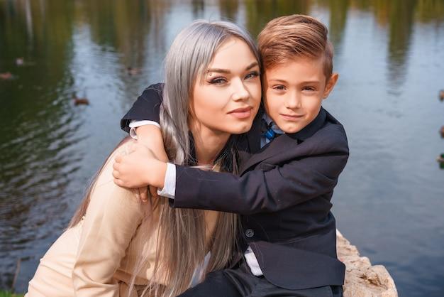 Feliz madre e hijo abrazando al aire libre junto al lago