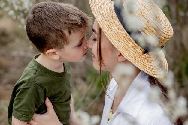 Feliz madre e hijo divirtiéndose juntos. la madre abraza suavemente a su hijo. en el fondo florecen flores blancas. día de la madre.