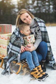 Feliz madre e hijo divirtiéndose con trineo en un bosque de invierno