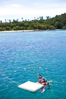 Feliz madre e hijo esnórquel divirtiéndose en el agua del océano esnórquel en vacaciones caribeñas en tailandia