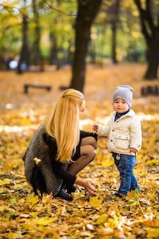Feliz madre e hijo están jugando en el parque de otoño