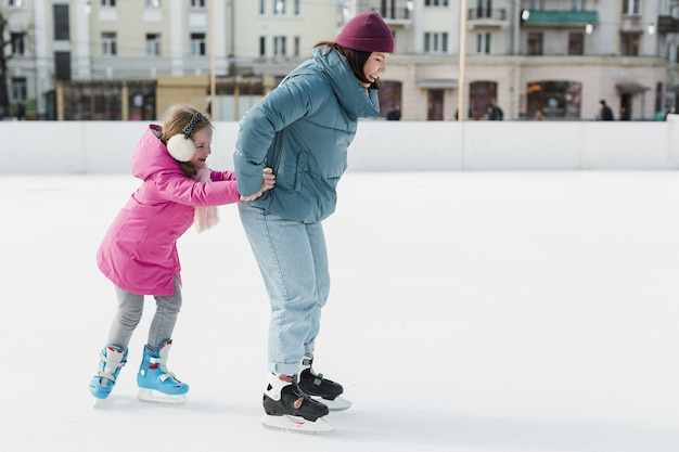 Feliz madre e hijo patinaje sobre hielo
