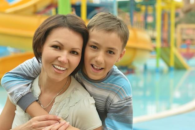 Feliz madre e hijo en resort de vacaciones junto a la piscina